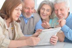 Senior couples reading newspaper Royalty Free Stock Image