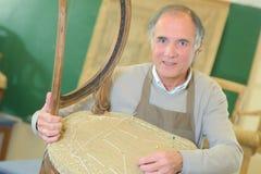 Senior craftman fixing chair Stock Photos