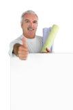Senior craftsman putting wallpapers Royalty Free Stock Image
