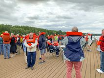 Senior cruisers during safety drill. Baja, Hungary - May 23, 2019 :  Senior tourists on river cruise participating in safety drill on deck of ship stock photos