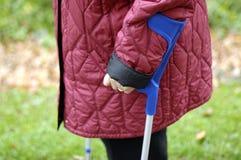 Senior on crutches Royalty Free Stock Photography
