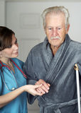 Senior on Crutches Assisted by His Nurse. Nurse helping a senior man on crutches - vertical Stock Image