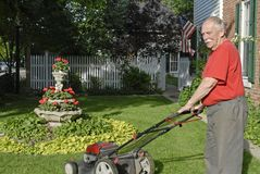 Senior Ctizen Mowing Lawn. Elderly man mowing the lawn with landscaping and white picket fence in the background Stock Photography