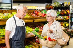 Senior customer and worker discussing vegetables. In supermarket Stock Photography