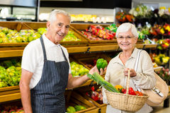 Senior customer and worker discussing vegetables. In supermarket Royalty Free Stock Photos