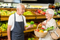 Senior customer and worker discussing vegetables. In supermarket Royalty Free Stock Images