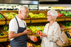 Senior customer and worker discussing vegetables. In supermarket Stock Photo