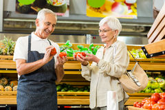 Senior customer and worker discussing vegetables. In supermarket Stock Photos