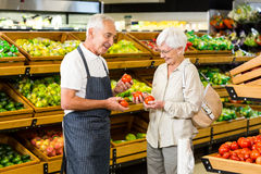 Senior customer and worker discussing vegetables. In supermarket Royalty Free Stock Photo