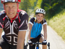 Senior cyclist. Senior man and young woman on road bike. Focus on background Stock Images