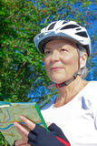 Senior cyclist helmet map orientation. Senior woman outdoors in the summer sun with bicycle helmet, protective gloves, white t-shirt and map, looking for her Royalty Free Stock Photos