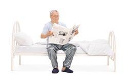 Senior czyta gazetę sadzającą na łóżku w piżamach Obrazy Royalty Free