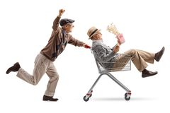 Senior with 3D glasses pushing a shopping cart with another seni Royalty Free Stock Photo