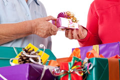 Senior and daughter reaching gift to each other Royalty Free Stock Photography