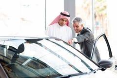 Senior dealer car. Senior dealer pointing car features to potential Arabian buyer Stock Image