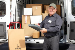 Senior delivery man with parcel near truck. Stock Photo