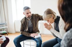 A senior depressed woman crying during group therapy. royalty free stock images