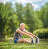 Senior, der Übungen im Park ausdehnend tut Stockfotos