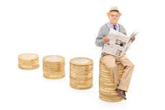 Senior, der die Nachrichten gesetzt auf einem Stapel von Münzen liest Lizenzfreies Stockbild