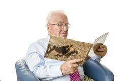 Senior, der ein Bilderbuch liest Stockfoto