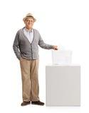 Senior, der eine Abstimmung in eine Wahlurne abgibt Stockfotografie