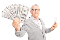 Senior, der eine Energiesparende Glühlampe und ein Geld hält Lizenzfreies Stockbild