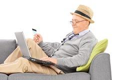 Senior, der eine Kreditkarte hält und an Laptop arbeitet Lizenzfreie Stockfotos