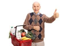 Senior, der einen Korb hält und Daumen aufgibt Stockfotografie
