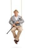 Senior, der einen Stock hält und auf einem Schwingen sitzt Stockfoto