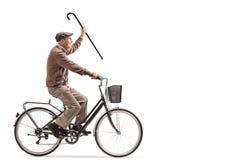 Senior, der einen Stock hält und Fahrrad fährt lizenzfreies stockfoto