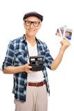 Senior, der einige Fotos und eine Kamera hält Lizenzfreies Stockbild