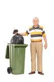 Senior, der heraus den Abfall wirft Stockbild