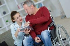 Senior, der herein Tablette im Rollstuhl zu Hause verwendet Lizenzfreies Stockbild
