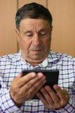 Senior, der moderne digitale Tablette verwendet Stockbilder