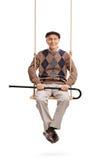 Senior, der seinen Stock hält und auf einem Schwingen sitzt Stockfotografie