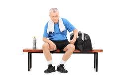 Senior in der Sportkleidung, die auf einer Bank sitzt Lizenzfreies Stockbild