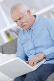 Senior, der zu Hause Laptop verwendet Stockbilder