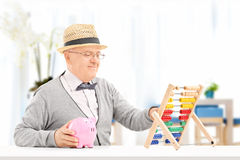 Senior, der zu Hause seine Einsparungen mit Abakus zählt Stockfoto