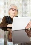 Senior, der zu Hause Tablettengerät verwendet Lizenzfreie Stockfotografie