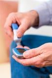 Senior with diabetes using blood glucose analyser Stock Image