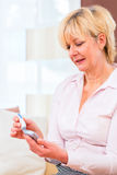 Senior with diabetes using blood glucose analyser Stock Photo