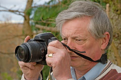 Senior with digital camera. An image of a Senior in the garden photographing birds and wildlife with a Royalty Free Stock Images