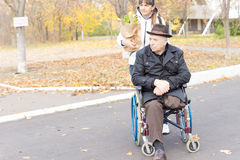Senior disabled man being helped with his shopping stock photos