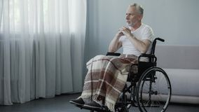 Senior disabled man sitting in wheelchair and looking in window, waiting family Royalty Free Stock Photography