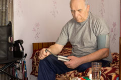 Senior disabled man taking his own blood pressure Stock Image