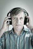 Senior DJ. Senior male listening to music through headphones royalty free stock photo