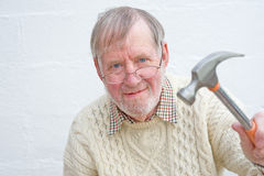 Senior and Do-it-yourself. A closeup  image of a smiling senior holding a hammer and a keen believer in 'do-it-yourself Royalty Free Stock Photo
