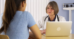 Senior doctor advising Hispanic woman patient Royalty Free Stock Image