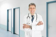 Senior doctor with arms crossed standing in hospital Stock Images