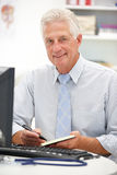 Senior doctor at desk Royalty Free Stock Images